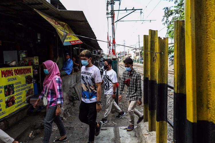 Pekerja menggunakan masker saat melintasi rel kereta di Jalan Tanjung Selor, Grogol, Jakarta Barat, Senin (24/8/2020). Gubernur DKI Jakarta Anies Baswedan memutuskan untuk kembali memperpanjang pembatasan sosial berskala besar (PSBB) yang keempat kalinya terhitung mulai Jumat (14/8/2020) sampai 27 Agustus 2020.