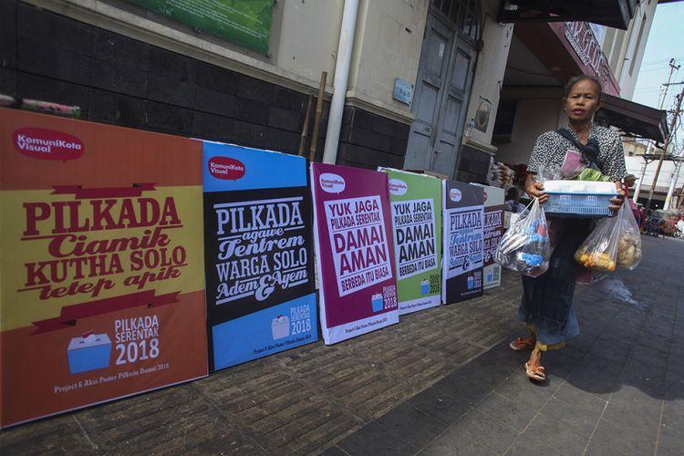 Pedagang melewati jajaran poster Pilkada Damai 2018 yang dipajang di kawasan Pasar Gede, Solo, Jawa Tengah, Senin (25/6/2018). Aksi yang digelar komunitas Komunikota Visual tersebut untuk mengajak warga menggunakan hak pilih dalam Pilkada Serentak pada 27 Juni mendatang serta berusaha mewujudkan berlangsungnya pilkada yang damai.