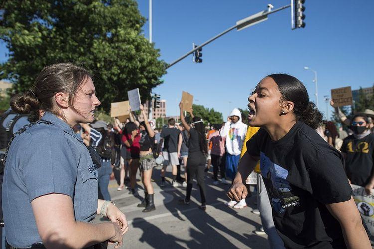 Dalam foto 29 Mei 2020 ini, seorang polisi wanita berdiri ketika seorang wanita muda berteriak padanya pada sebuah protes atas kematian George Floyd selama bentrokan di Country Club Plaza di Kansas City.
