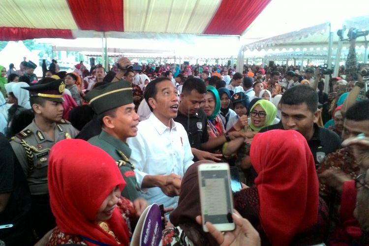 Presiden Jokowi melayani warga Kabupaten Gowa bersalaman dan berswafoto di bawah guyuran hujan, Kamis (15/2/2018).