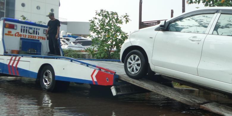 Sabtu (4/6/2016), mobil derek Dinas Perhubungan menderek mobil yang terendam banjir