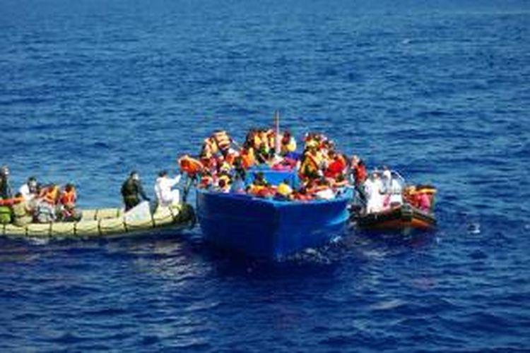 Dalam foto yang diambil pada 8 September 2014 ini terlihat tim penyelamat AL Italia membantu para pengungsi keluar dari perahu mereka di Laut Tengah. Para imigran itu berangkat dari Afrika menuju ke Eropa untuk mengadu nasib.