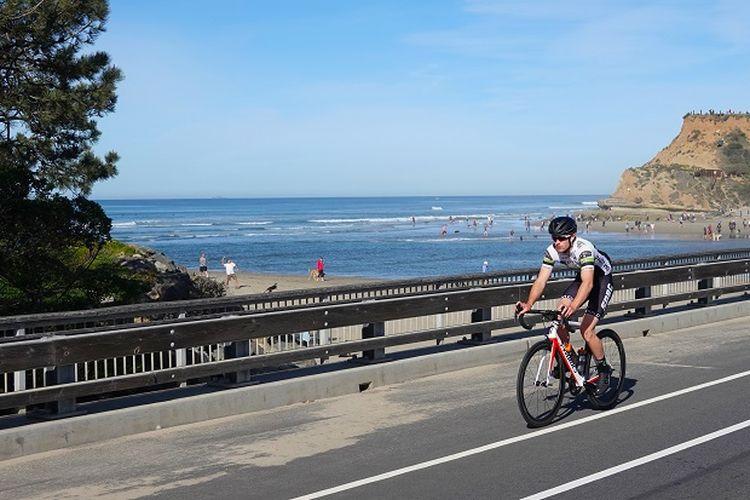 Ilustrasi pengendara sepeda - Seorang pengendara sepeda melintasi jalur dekat sebuah pantai di California, AS.