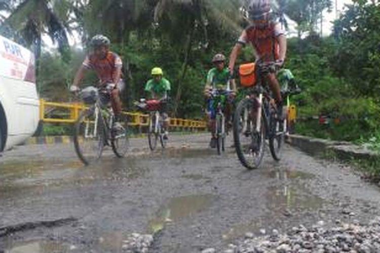 Peserta Jelajah Sepeda Sabang-Padang melintasi jalan rusak di Desa Surung Mersada, Kecamatan Kerajaan, Kabupaten Pak Pak Barat, Sumatera Utara, Jumat (6/9/2013).