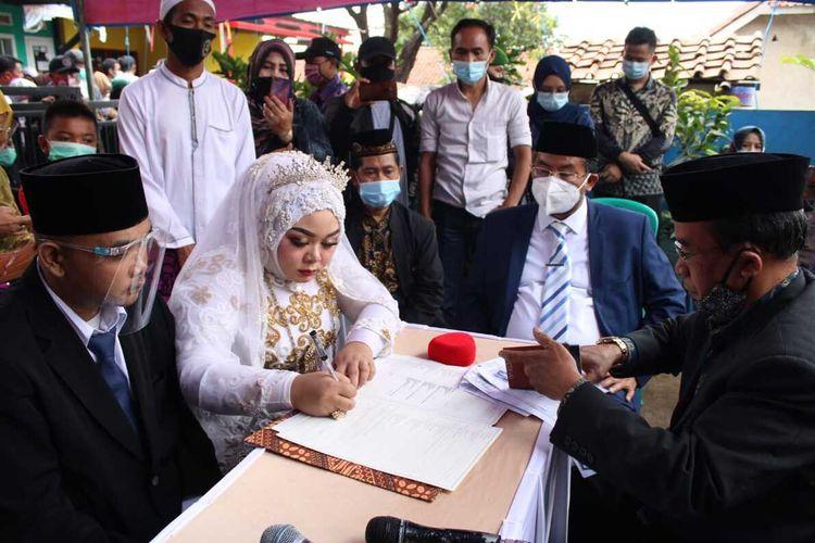 Akad nikah pasangan Indri dan Andri berlangsung khidmat di tengah duka mendalam karena harus kehilangan kedua orangtuanya dalam musibah longsor. Akad berlangsung di Desa Sawahdadap, Cimanggung, Sumedang, Kamis (28/1/2021). Wakil Bupati Sumedang jadi saksi nikah keduanya.