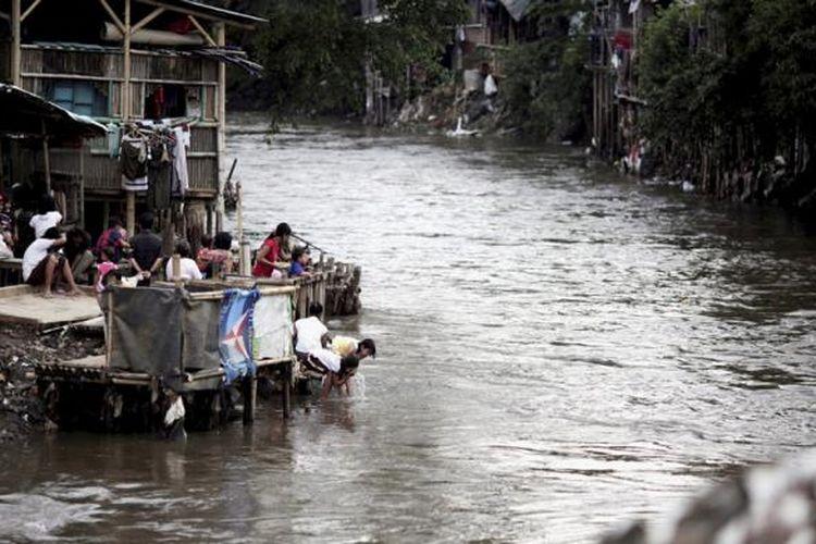 Anak-anak mencuci muka di Kali Ciliwung yang penuh dengan hunian di Kampung Pulo, Kelurahan Kampung Melayu, Kecamatan Jatinegara, Jakarta Timur, Minggu (15/2/2015). Pencemaran sungai di Jakarta sudah jauh di atas ambang batas yang diisyaratkan. bahkan, dari sekitar 807.000 pelanggan air dari dua perusahaan air minum di DKI Jakarta, hampir 300.000 di antaranya tidak terlayani.
