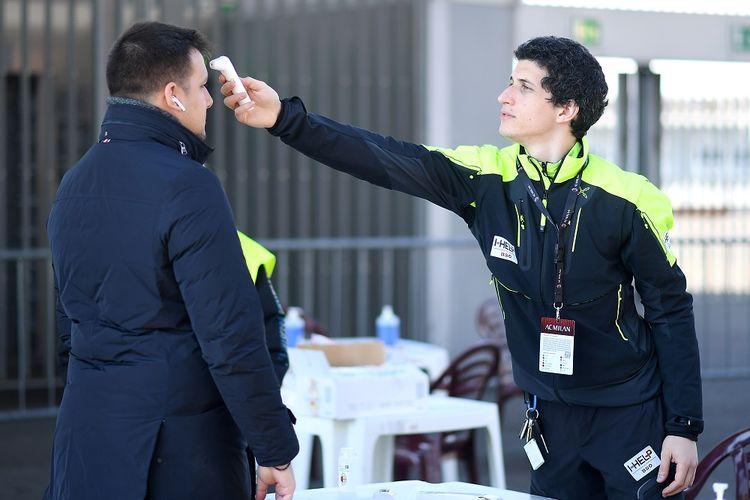 Staf memeriksa suhu badan seorang pria sebelum masuk ke stadion di San Siro, Milan, Italia, Minggu (8/3/2020). Pertandingan antara AC Milan melawan Genoa dilaksanakan di ruang tertutup untuk penonton saat jumlah kasus positif virus korona semakin meningkat. ANTARA FOTO/REUTERS/Daniele Mascolo/hp/cfo