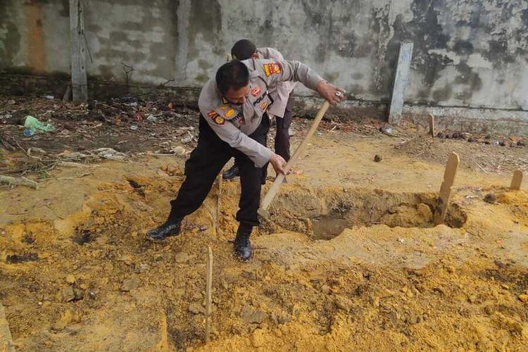 Petugas Polsek Tampan menutup kembali belasan kuburan yang ambles di TPU Beringin, Kelurahan Sei Sibam, Kecamatan Bina Widya, Kota Pekanbaru, Riau, Sabtu (17/4/2021).