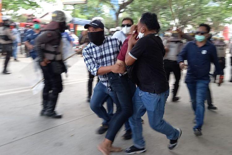 Seorang mahasiswa ditangkap polisi saat demostrasi penolakan omnibus law UU Cipta Kerja di depan kantor DPRD Kaltim, Samarinda, Jalan Teuku Umar, Kamis (8/10/2020).