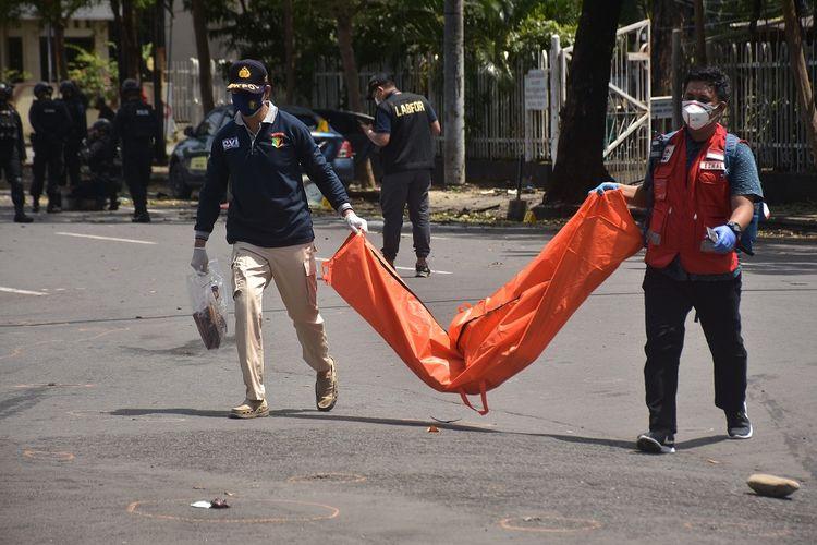 Petugas mengangkat kantong jenazah berisi bagian tubuh dari terduga pelaku bom bunuh diri di depan Gereja Katedral Makassar, Sulawesi Selatan, Minggu (28/3/2021). Bagian tubuh jenazah tersebut selanjutnya dibawa ke Rumah Sakit Bhayangkara Makassar untuk diidentifikasi. ANTARA FOTO/Indra Abriyanto/AP/wsj.