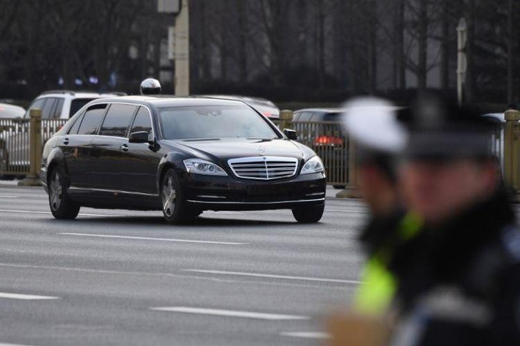 Mobil limosin dalam iring-iringan kendaraan pemimpin Korea Utara Kim Jong Un melewati polisi yang berjaga di sepanjang jalan utama timur-barat Changan di Beijing, China, Senin (9/1/2019). (AFP/Greg Baker)