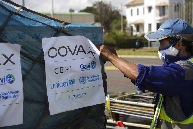 Pekerja bandara menyemprotkan kargo vaksin Covid-19 dari skema Covax setibanya di Antananarivo, Madagaskar, Sabtu 8 Mei 2021.
