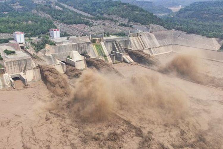Foto udara yang diambil pada 5 Juli 2021 ini menunjukkan air yang dilepaskan dari Bendungan Waduk Xiaolangdi di Luoyang di provinsi Henan, China tengah.