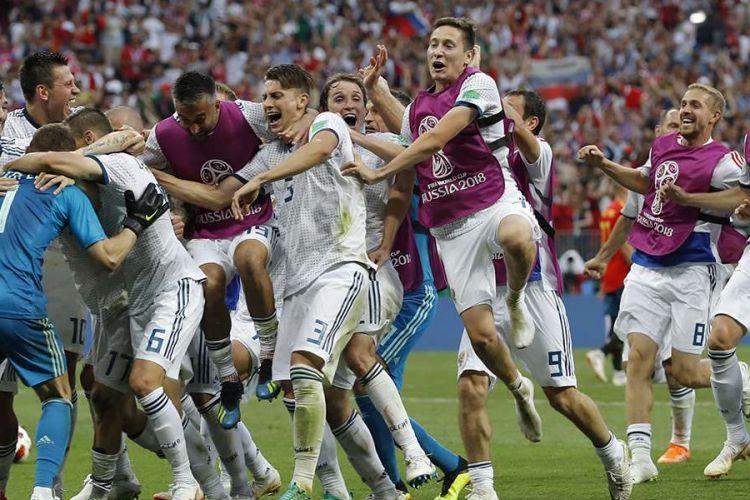 Para pemain Rusia berlari dan memeluk kiper Rusia Igor Akinfeev yang berhasil menggagalkan dua tendangan dalam adu penalti pada laga 16 besar Piala Dunia 2018 melawan Spanyol di Stadion Luzhniki, Minggu (1/7/2018). Timnas Rusia lolos ke babak perempat final setelah menyingkirkan Spanyol lewat drama adu penalti dengan skor 4-3.