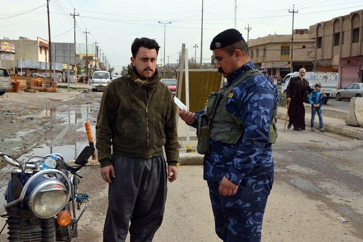 Seorang polisi tengah memeriksa identitas pengendara motor di Mosul, Irak, pada 22 Februari 2018 lalu.