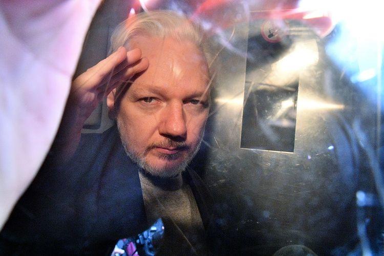 Pendiri WikiLeaks Julian Assange memberi isyarat dari jendela sebuah mobil van yang membawanya ke penjara dari Southwark Crown Court di London, Inggris, pada 1 Mei 2019. (AFP/DANIEL LEAL-OLIVAS)