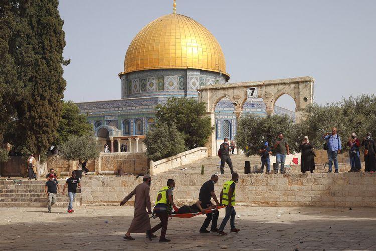 Warga Palestina mengevakuasi seorang pria yang terluka selama bentrokan dengan pasukan keamanan Israel di kompleks Masjid Al-Aqsa, Yerusalem Senin,(10/5/2021). Polisi Israel kembali bentrok dengan pengunjuk rasa Palestina di tempat tersebut pada Senin. Petugas medis Palestina mengatakan setidaknya 180 warga Palestina terluka dalam kekerasan di kompleks Masjid Al-Aqsa, termasuk 80 orang yang dirawat di rumah sakit.