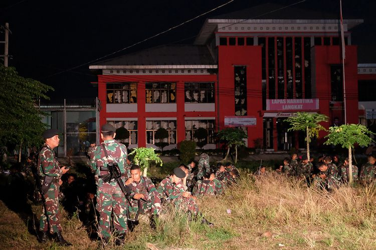 Prajurit TNI berjaga di depan Lapas Narkotika Kelas III Langkat pasca-kerusuhan yang terjadi, di Langkat, Sumatera Utara, Kamis (16/5/2019). Akibat peristiwa kerusuhan yang dilakukan para narapidana di Lapas tersebut mengakibatkan tiga mobil petugas rusak terbakar dan ratusan napi melarikan diri.