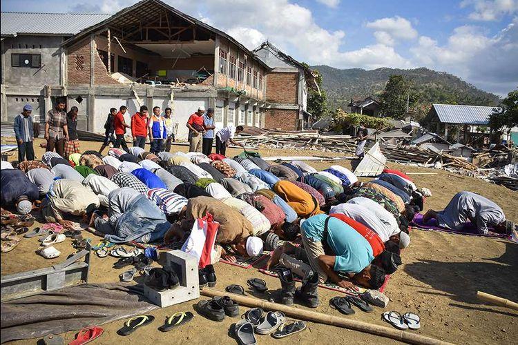 Sejumlah warga korban gempa menunaikan shalat Ashar saat menunggu Presiden Joko Widodo tiba untuk memberikan bantuan, di Desa Pemenang Barat, Kecamatan Pemenang, Tanjung, Lombok Utara, NTB, Minggu (2/9/2018). Sebanyak 5.293 korban gempa dari Lombok Utara, Lombok Timur, Lombok Tengah dan Mataram menerima bantuan berupa tabungan sebesar Rp 50 juta untuk perbaikan rumah yang rusak berat dan Rp 25 juta untuk rumah yang rusak ringan.