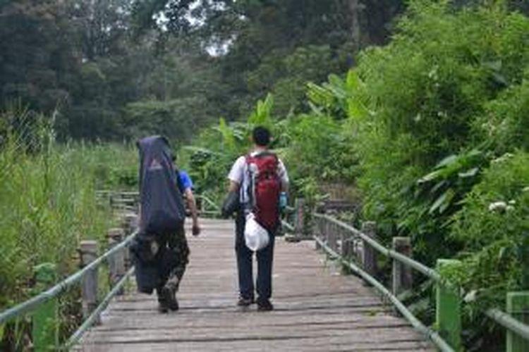 Pendaki membawa kantung sampah melalui jalur jembatan saat pendakian Gunung Gede, Bogor, Jawa Barat