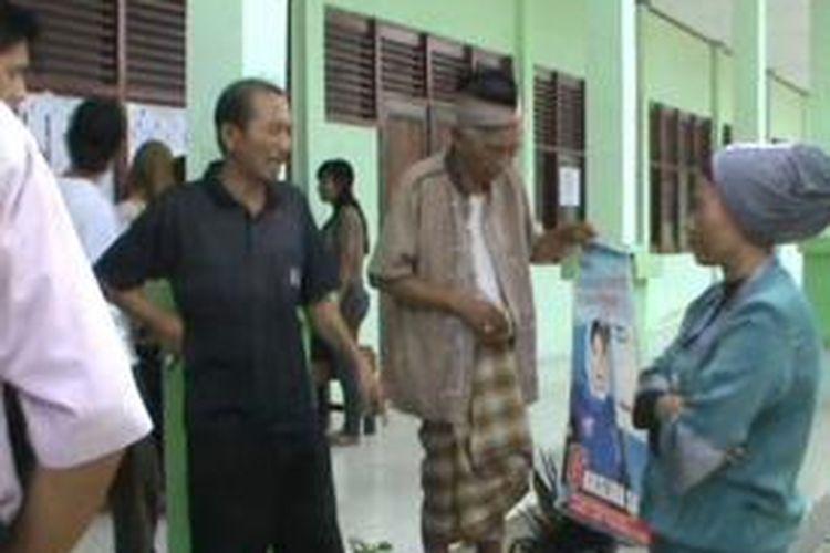 Saleh, Kakek 85 tahun menneteng poster caleg idola pilihannya ke TPS rabu (9/4/2014)