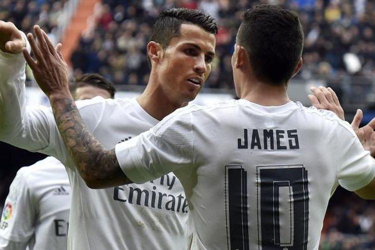 Gelandang Real Madrid asal Kolombia, James Rodriguez (kanan), mendapat sambutan dari Cristiano Ronaldo, usai mencetak gol ke gawang Athletic Bilbao pada pertandingan La Liga di Santiago Bernabeu, Sabtu (13/2/2016).