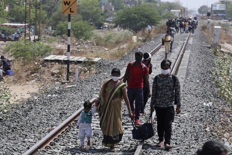 Pada Senin (11/5/2020), di foto ini, tampak pekerja migran dari negara bagian di India berjalan pulang ke kampung halaman mereka melalui rel kereta api menuju stasiun kereta api di Ahmedabad, India.
