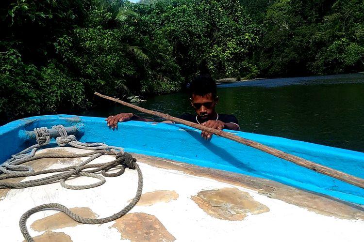 Mundi Daman, siswa kelas XI di sebuah SMA di Waisai, Kabupaten Raja Ampat, Papua Barat, menarik perahu motor yang membawa sejumlah wisatawan ke Kali Biru di distrik Teluk Mayalimbit, Raja Ampat, Jumat (4/5/2018).
