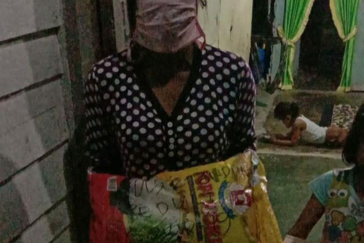 RMS (31), menerima bantuan sembako dari polisi, usai dilaporkan mencuri tandan buah sawit PTPN V Sei Rokan di Desa Tandun Barat, Kecamatan Tandun, Kabupaten Rohul, Riau, Selasa (2/6/2020). RMS mencuri tandan buah sawit dengan alasan untuk membeli beras.