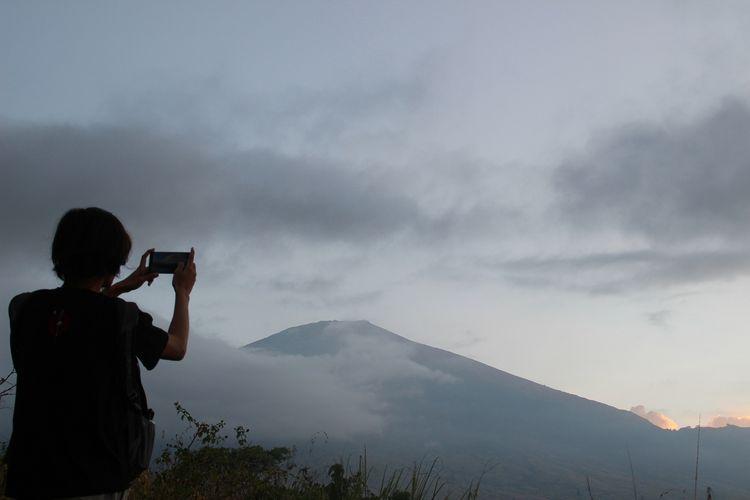 Seorang wisatawan mengabadikan keindahan Gunung Rinjani dari Desa Sembalun, Lombok Timur. Gunung Rinjani merupakan kawasan pendakian yang menjadi primadona di NTB.