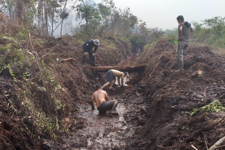 Dua personel Satpol PP Riau, Lerinardo dan Zulkifli masuk ke dalam kanal berlumpur mencari sumber air untuk memadamkan api karhutla di Desa Rimbo Panjang, Kecamatan Tambang, Kabupaten Kampar, Riau, Kamis (10/10/2019).