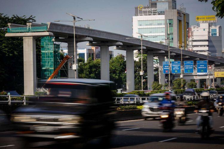 Pengendara melintas di samping lokasi pembangunan Light Rail Transit (LRT) Cawang-Pancoran di Jakarta, Sabtu (24/2/2018). Progres proyek pembangunan kereta api ringan atau Light Rail Transit (LRT) tahap I yang meliputi relasi Cibubur-Cawang, Bekasi Timur-Cawang dan Cawang-Dukuh Atas secara keseluruhan mencapai 20 persen dan ditargetkan selesai pada 2019.