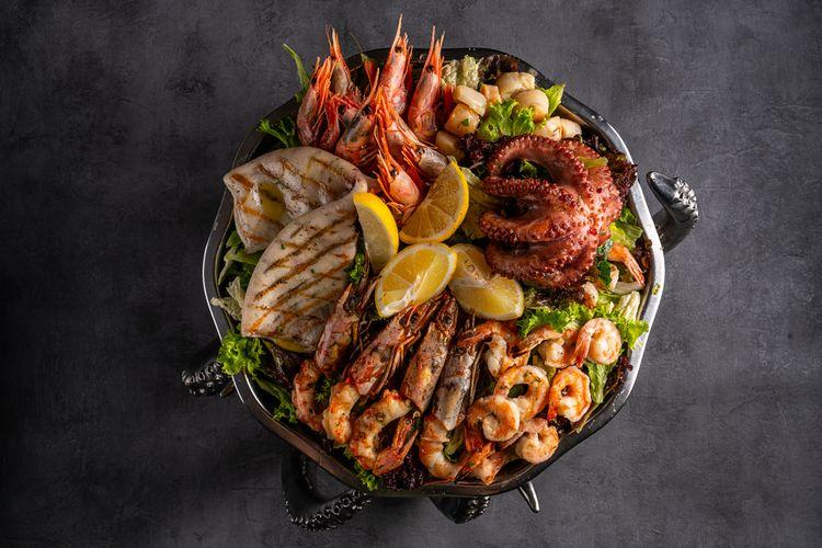 Ilustrasi seafood bakar terdiri dari kepiting, kerang, udang, cumi-cumi, dan ikan.
