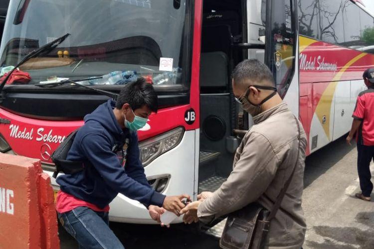 Sebelum berangkat menuju daerah tujuan, bus Medalsekarwangi dan pemudik disemprot disinfektan di terminal.