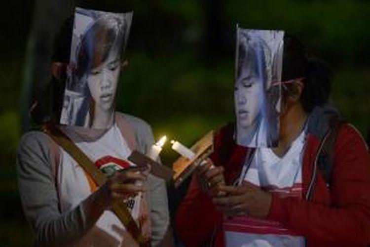 Pekerja migran menyalakan lilin dalam aksi mendukung terpidana mati asal Filipina Mary Jane Veloso di luar Istana Presiden, 27 April 2015.
