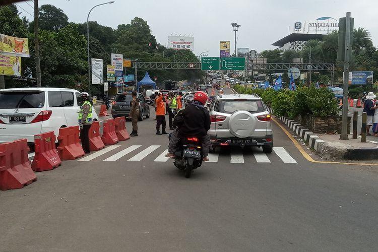 Sejumlah petugas gabungan mengkombinasikan rekayasa lalu lintas berupa ganjil genap dan sistem satu arah atau one way di Jalur Puncak Bogor, Jawa Barat, Minggu (19/9/2021).
