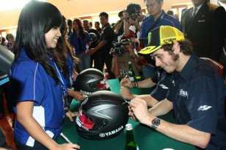Pebalap Movistar Yamaha asal Italia, Valentino Rossi, memberikan tanda tangan untuk penggemar saat berkunjung ke Jakarta, Indonesia, pada 2014.