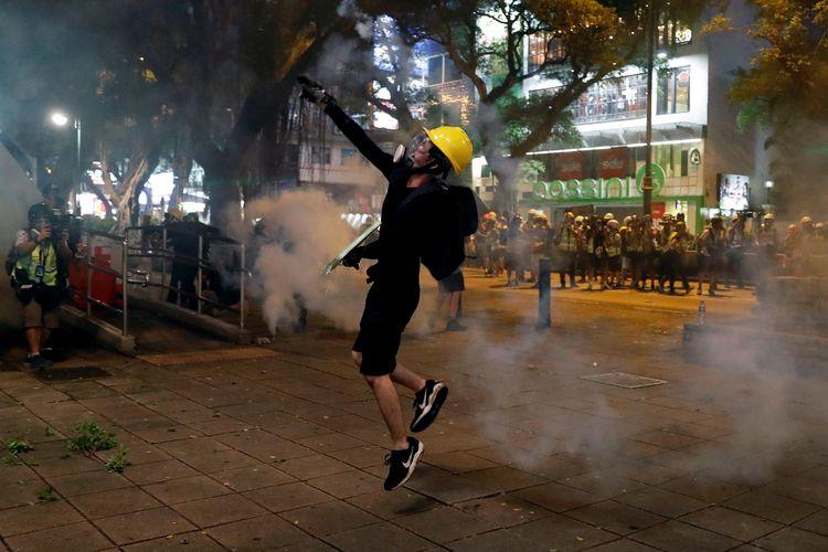 Seorang pengunjuk rasa anti rancangan undang-undang ekstradisi melempar gas air mata saat berunjuk rasa di Tsim Sha Tsui di Hong Kong, China, Minggu (11/8/2019).