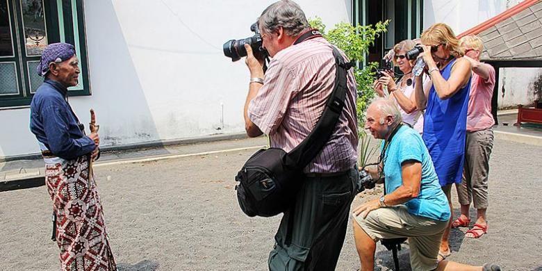 Sejumlah wisatawan mancanegara memotret seorang abdi dalem di Keraton Yogyakarta, Kamis (17/9/2015). Selama bulan September, kunjungan wisatawan mancanegara ke Keraton Yogyakarta relatif stabil, yakni sekitar 400 orang per hari.