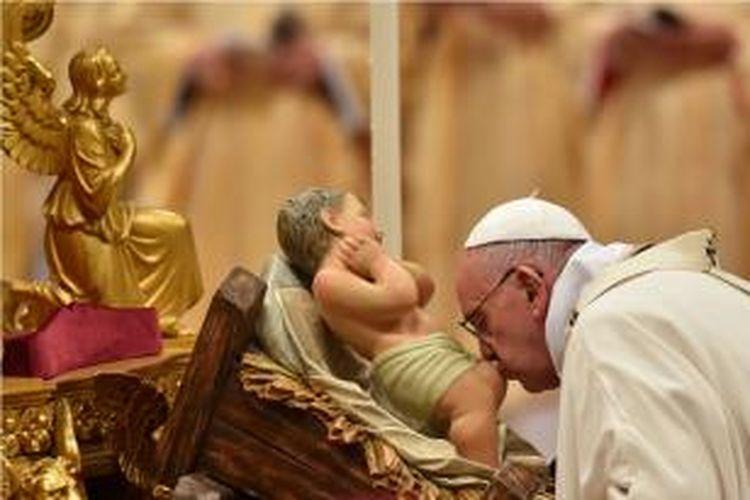 Paus Fransiskus mencium boneka bayi Yesus Kristus saat misa malam Natal di Gereja Basilika Santo Petrus, Vatikan, Kamis (24/12/2015).