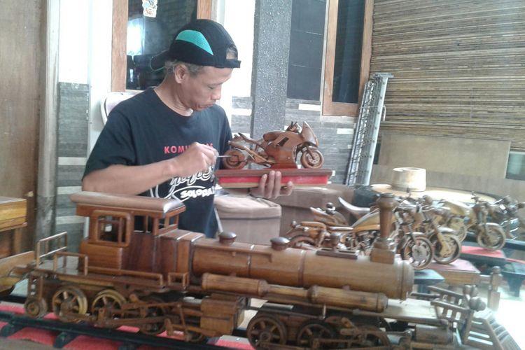 Perajin limbah kayu, Winarto (42), sedang merangkai miniatur sepeda motor Harley-Davidson di rumahnya, Sumber, Banjarsari, Solo, Jawa Tengah, Rabu (7/2/2018).