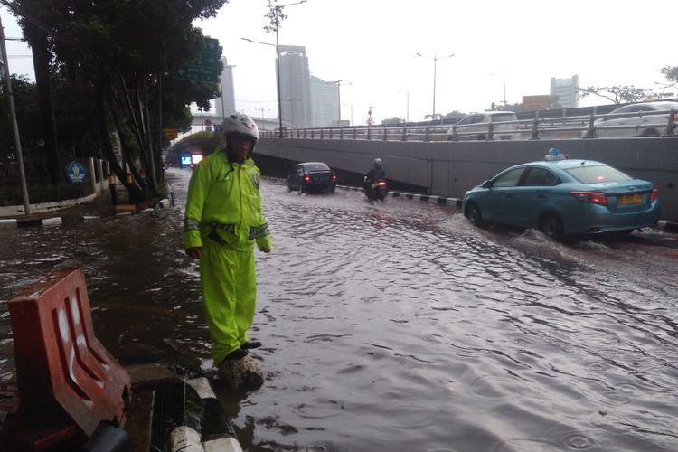 Petugas kepolisian mengatur lalu lintas saat genangan air terlihat di Jalan Gatot Subroto, Jakarta Pusat, Sabtu (18/1/2020).