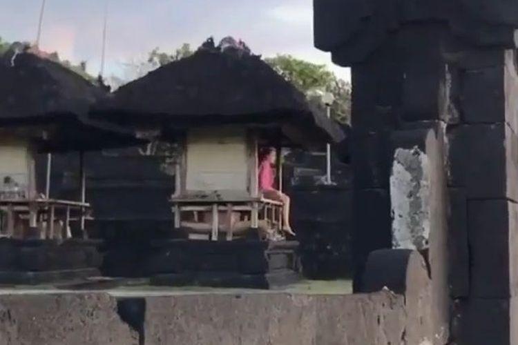 Potongan video yang menampilkan seorang warga negara asing duduk di areal Pura.