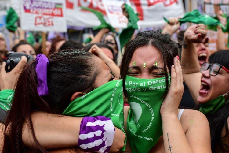 Para pengunjuk rasa pro-aborsi mengenaka kain hijau merayakan pengesahan undang-undang yang melegalkan aborsi di luar Kongres Argentina, di Buenos Aires, 30 Desember 2021.