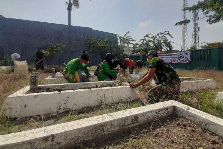 Anggota TNI bersama para pelajar saat membersihkan Taman Makam Pahlawan (TMP) yang ada di Kecamatan Menganti, Gresik, Senin (9/11/2020).