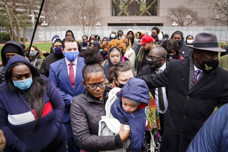 Chyna Whitaker (tengah) menggendong putranya, Daunte Jr, saat dia berjalan ke mikrofon untuk berbicara selama konferensi pers, Selasa (13/4/2021), di Minneapolis. Suami Chyna, Daunte Wright (20), ditembak mati oleh polisi pada Minggu (11/4/2021) di Brooklyn Center, Minneapolis.