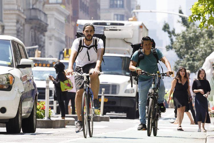 Pengendara sepeda melintas di persimpangan 23rd street and 6th avenue, New York, Amerika Serikat, (30/7/2019).
