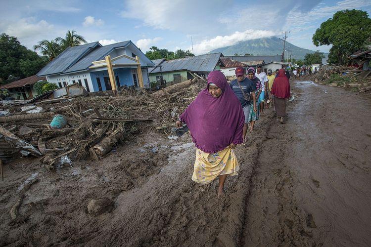 Sejumlah warga berusaha melewati jalan yang tertutup lumpur akibat banjir bandang di Adonara Timur, Kabupaten Flores Timur, Nusa Tenggara Timur (NTT), Selasa (6/4/2021). Cuaca ekstrem akibat siklon tropis Seroja telah memicu bencana alam di sejumlah wilayah di NTT dan mengakibatkan rusaknya ribuan rumah warga dan fasilitas umum. ANTARA FOTO/Aditya Pradana Putra/wsj.