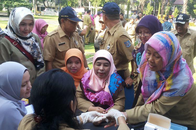 Para pegawai negeri sipil (PNS) di lingkungan Pemerintah Kota Depok mengikuti tes untuk mengecek kadar kolesterol dan gula darah yang diadakan di halaman Balai Kota Depok, THR PNS 2021 Senin (3/7/2017).