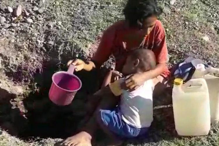 Seorang warga Desa Reroroja, Kecamatan Magepanda, Kabupaten Sikka saat mengambil air di lubang yang mereka gali di bantaran sungai, Selasa (10/9/2019).